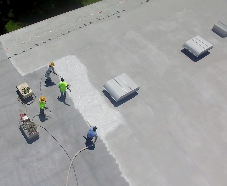 A crew of roofers spraying a silicone roof coating on a flat roof