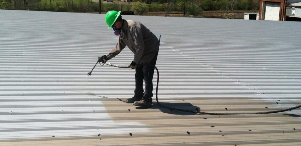 A worker applying a spray-on silicone roof coating.